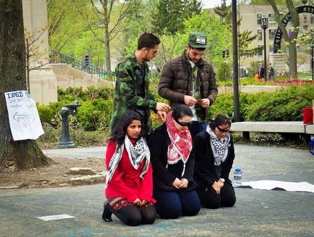 Students participate in a mock Israeli checkpoint stop near The Rock on Tuesday. Students for Justice in Palestine and MEChA de Northwestern organized the demonstration.