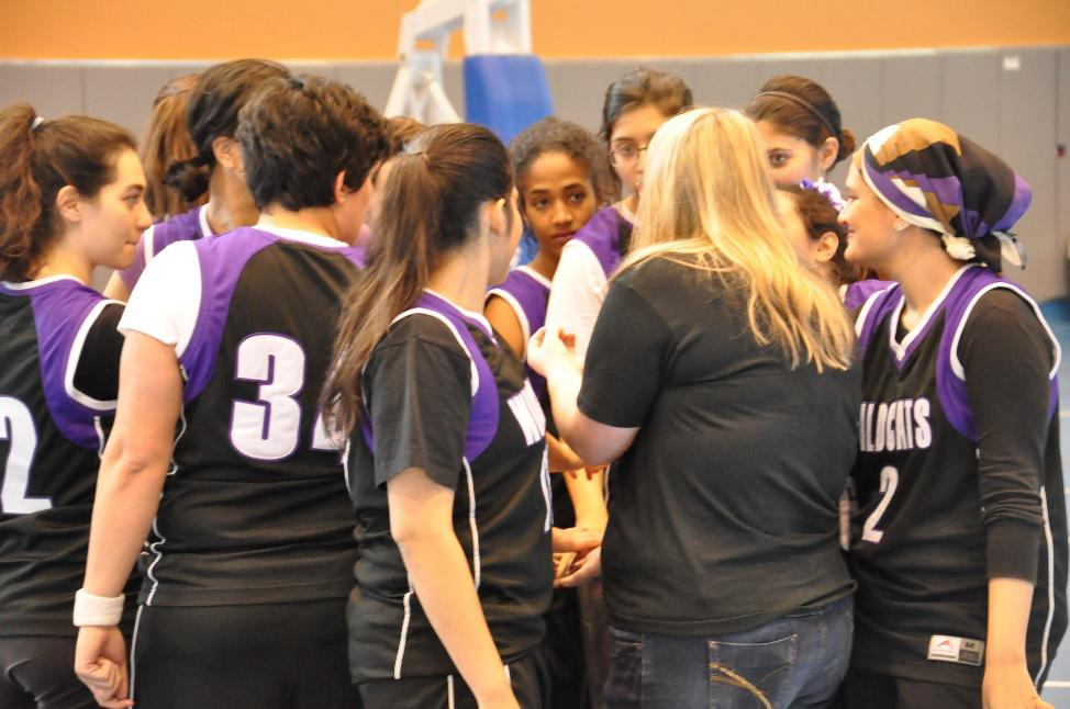 The NU-Qatar women's basketball team huddles up during a game. The squad has a heavy emphasis on teaching teamwork and fundamentals to its often inexperienced players.