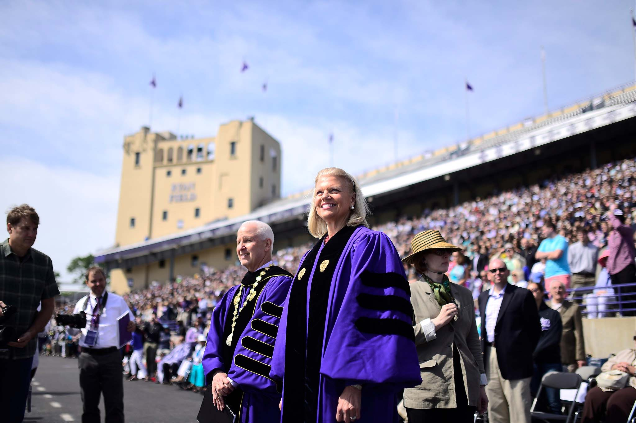 Virginia Rometty, IBM chairwoman and CEO, enters Ryan Field for Friday's commencement ceremony alongside University President Morton Schapiro. Rometty gave this year's commencement address to an audience of 15,000 graduates, faculty and guests.