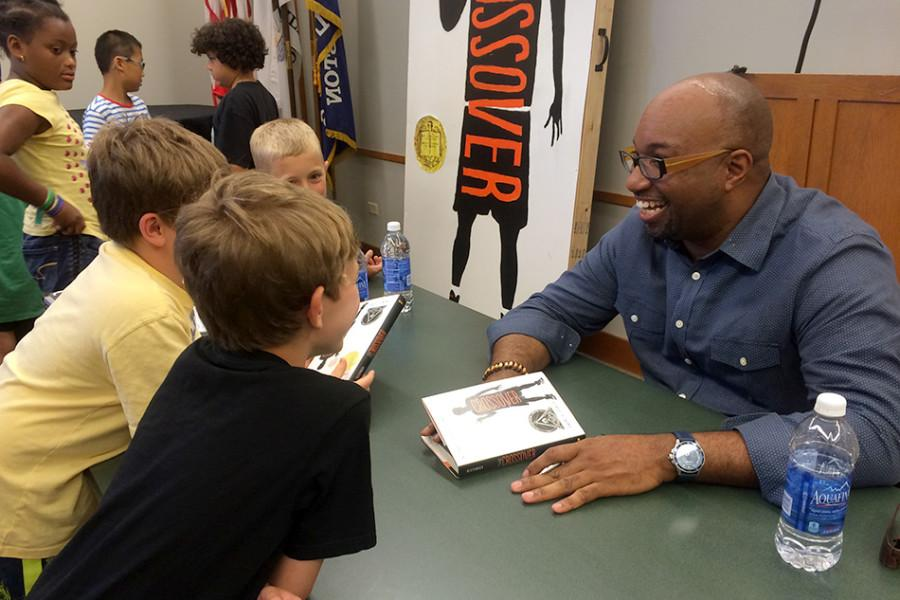 Kwame+Alexander%2C+this+year%27s+Newbery+Medalist%2C+signs+copies+of+his+award-winning+book+Thursday+afternoon+at+the+Evanston+Public+Library.+Alexander%27s+book%2C+called+%22The+Crossover%2C%22+is+a+children%27s+novel+about+basketball-playing+twins+that+is+written+entirely+in+verse.+