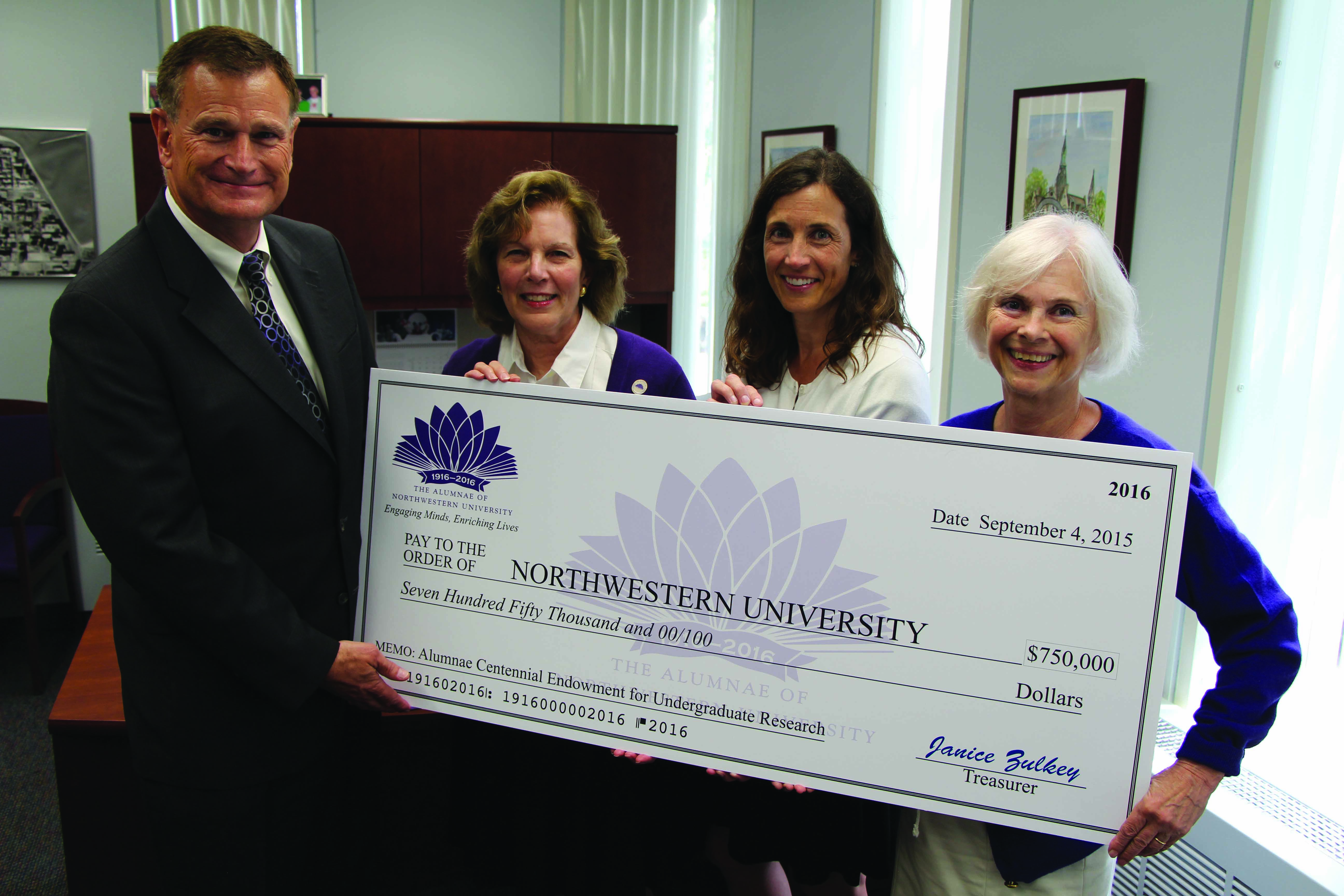 Ron Braeutigam, Pam James, Anne Martino and Janet Bilandic present a $750,000 check at the Northwestern Alumni Association Leadership Symposium. The Alumnae created a $1 million endowment for undergraduate research at NU.