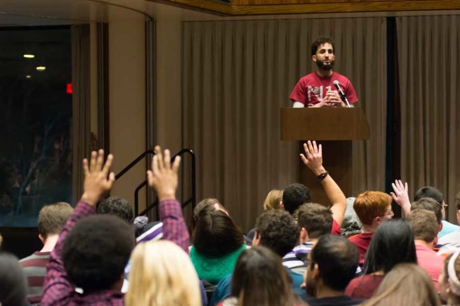 "Students raise their hands in ""silent applause"" as an NUDivest member speaks in favor of the collective's resolution at The Senate's Feb. 18 meeting. The body would go on to pass the resolution at the end of the meeting."