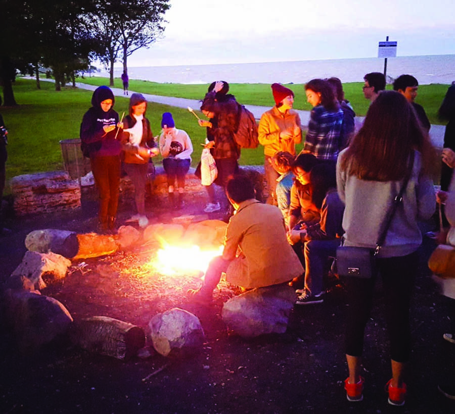 """Students gather at the bonfire held by Real Food at NU on Wednesday evening at the lakefill. The organization started posting banners promoting """"local, sustainable, humane or fair trade"""" food in all dining halls."""
