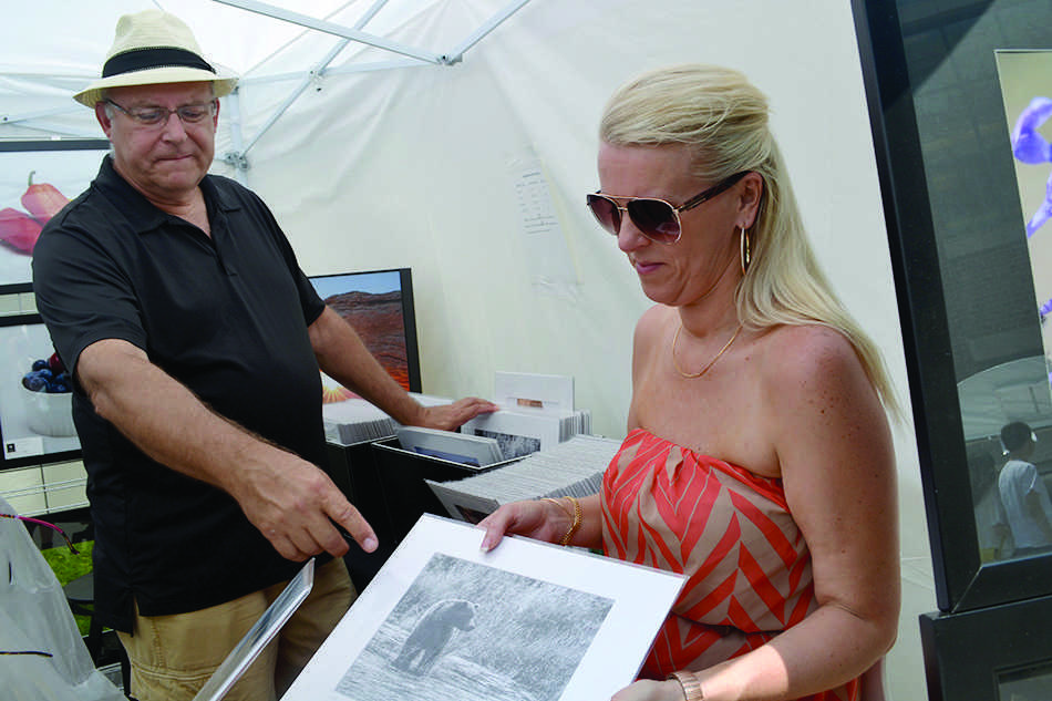 Jerry Alt (left), an Evanston-based photographer, shows his nature photography alongside his business partner Annette Patko at a June art festival in the city. Alt is debuting on Sunday a collection of his photography from his trip to Cuba.