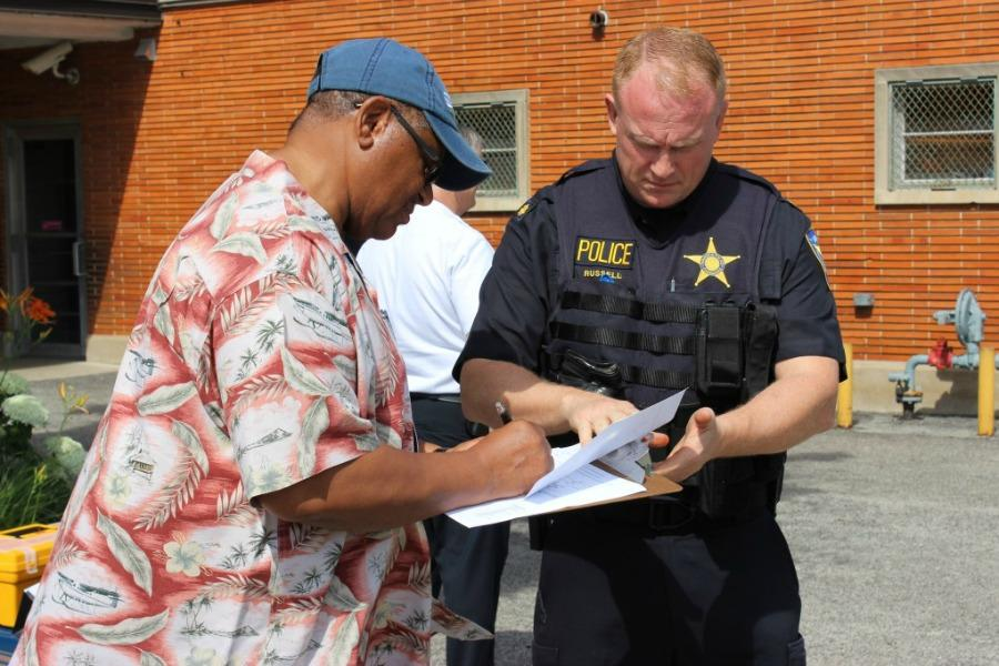 Evanston resident James Davis fills out paperwork at the city's second gun buyback event in June 2013. The city has since changed the gun buyback format to allow residents to trade guns for money on a daily basis.