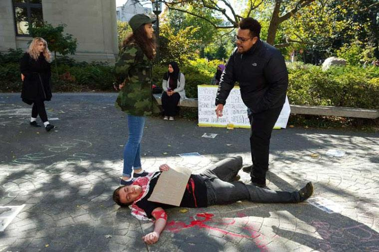 An+NU+student+lies+on+the+ground+near+The+Rock+while+dressed+as+a+wounded+Palestinian+boy.+The+demonstration+was+hosted+by+NU+SJP+on+Wednesday+and+imitated+a+viral+video+of+a+violent+scene+in+Israel.+