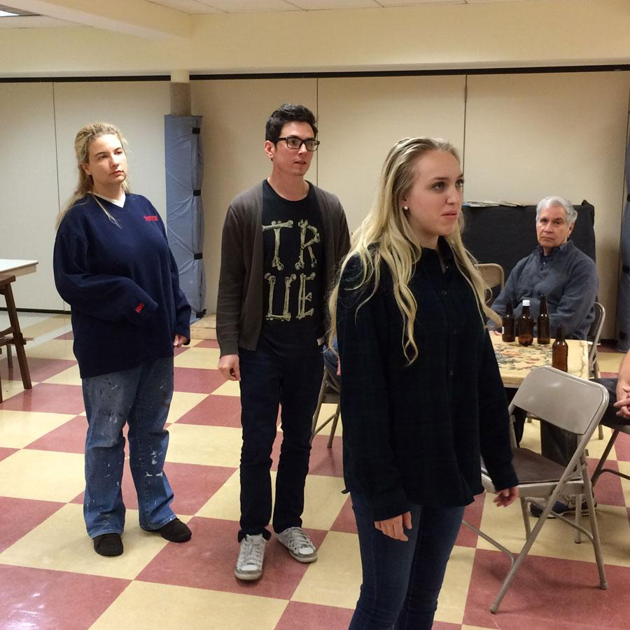 """Cast members Gina Palmer, Bryan Jansyn, Bailey Lawrence and John Frank (Medill '76) rehearse a scene from """"Boys in the Basement."""" The show, put on by the 2nd Act Players, opens on Nov. 6 at the Noyes Cultural Arts Center."""
