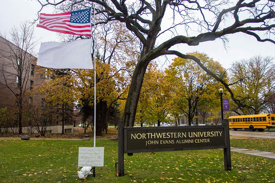 A white flag flies beneath the American flag at the John Evans Alumni Center in commemoration of the 151st anniversary of the Sand Creek Massacre Saturday morning. The Northwestern Native American and Indigenous Student Alliance launched a petition to rename the alumni center Saturday during the final event of this year's MSA Native American Heritage month.