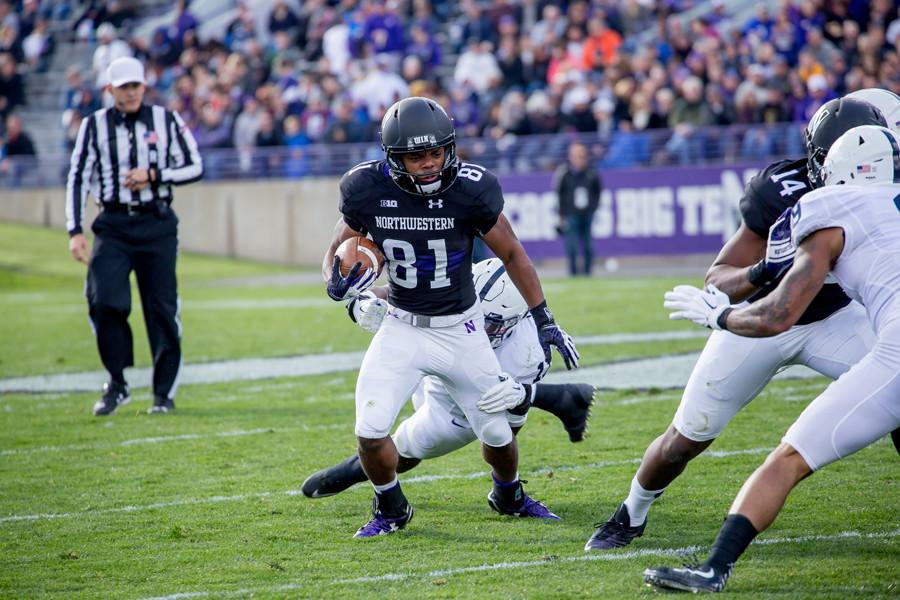Freshman Jelani Roberts runs behind a block thrown by senior Christian Jones. Despite contributions from players with many different skillsets, the Northwestern receiving corps as a whole has struggled this year.