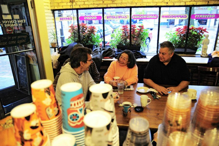 Darush Mabadi, Katherine Week and Bob Hariman sit at a communal table in Unicorn Cafe discussing politics and literature. They are part of a larger group of about 15 people who have been meeting daily for more than 25 years.