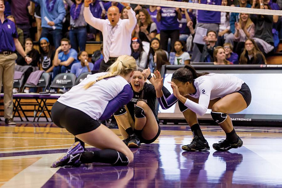 """Caroline """"Carks"""" Niedospial (center) celebrates after a win. With the senior libero's impressive career coming to a close, NU may have a challenge replacing her next season."""