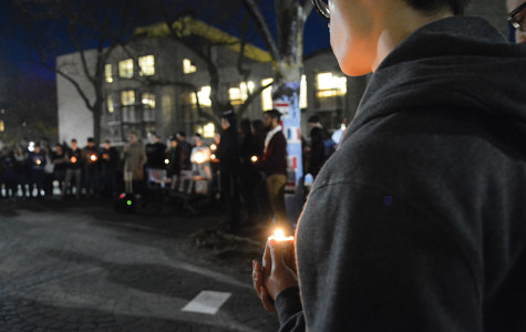 Members of the Northwestern community gather and pray at The Rock at a candlelight vigil. International Student Association and Interfaith hosted the vigil Sunday evening to support those who were affected by the recent terrorist attacks worldwide.