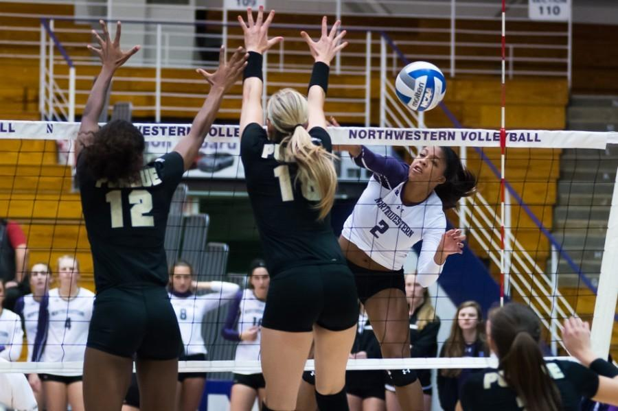 Symone Abbott spikes the ball past two defenders. The sophomore outside hitter has been racking up kills in recent games, including 17 in NU's victory over Michigan State on Saturday.