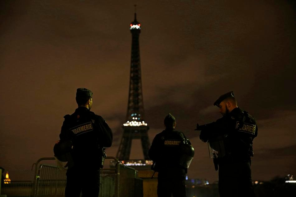 Armed police stand guard on Saturday, November 14, 2015, overlooking the Eiffel Tower, which was kept dark in honor of those who died in the terrorist attacks in Paris on Friday. France declares a national state of emergency after at least 120 people were killed in gun and bomb attacks.
