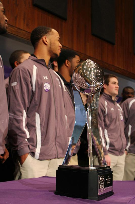 Northwestern football players stand behind their Gator Bowl trophy. The Cats won the Gator Bowl in 2013, ending a decades-long bowl losing streak.