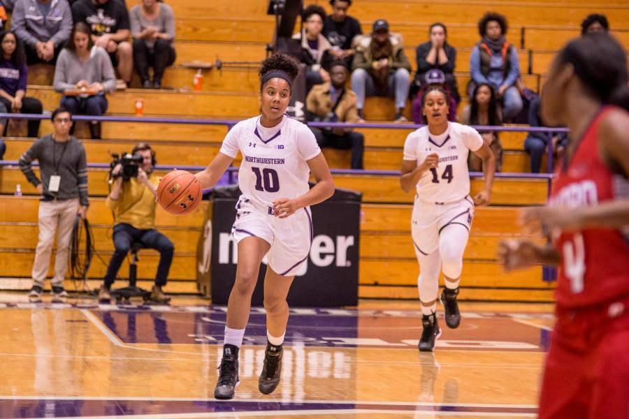 Caption: Nia Coffey dribbles down the court. The junior forward played out of position at center for most of Saturdays game against DePaul.