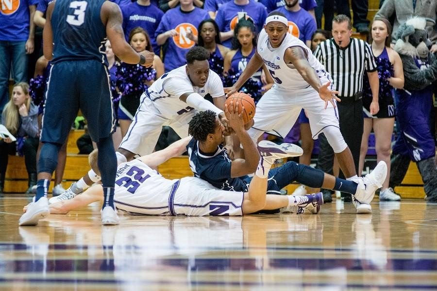 Three Wildcats try to grab a loose ball. Northwestern was out-rebounded by the Nittany Lions 42 to 34 in Saturday's 71-62 defeat.