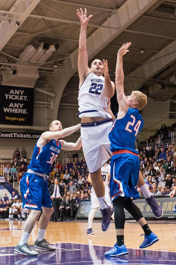 Alex Olah goes for the basket. Ever since the senior center was sidelined with a stress fracture in his foot, Northwestern has struggled on offense.