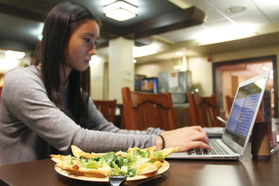 A+student+peers+at+her+laptop+while+eating+at+Fran%27s+Cafe%2C+a+late-night+cafe+run+by+Northwestern+Dining.+The+University+has+its+contracts+with+food+service+provider+Sodexo+up+for+renewal+in+2018.
