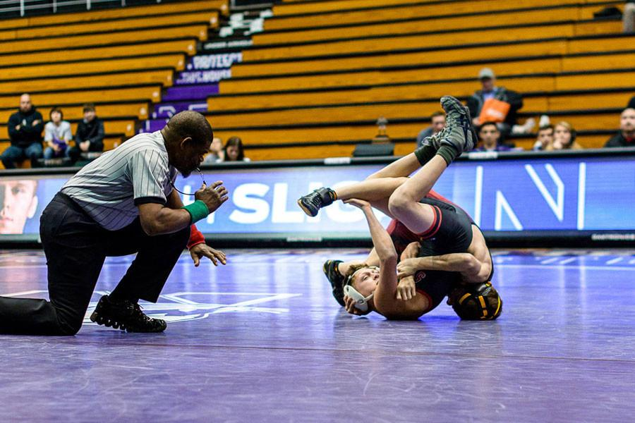 A Northwestern wrestler pins his opponent. The Wildcats will look to turn around their disappointing season Sunday against Iowa.