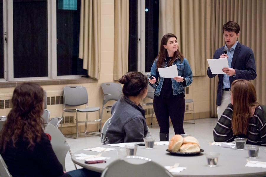 """Weinberg senior Brad McCandless (right) and SESP junior Sarah Thompson host a """"hunger banquet"""" in Parkes Hall on Wednesday night. The 2016 Dance Marathon emcees led a presentation on the effects of hunger and poverty around the world."""