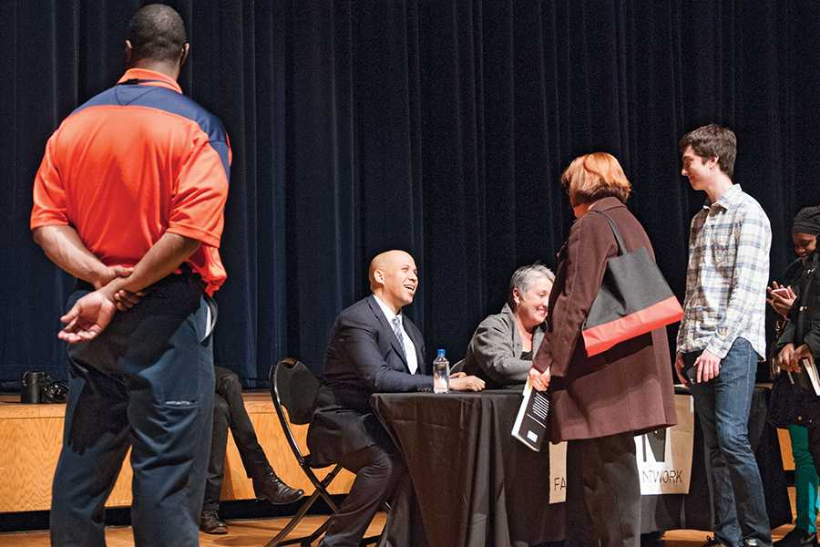 Sen. Cory Booker (D-N.J.) greets attendees at his speech at Evanston Township High School on Friday evening. Booker spoke to a packed auditorium as part of an event that also featured speeches from Sen. Dick Durbin (D-Ill.) and Rep. Jan Schakowsky (D-Ill.).