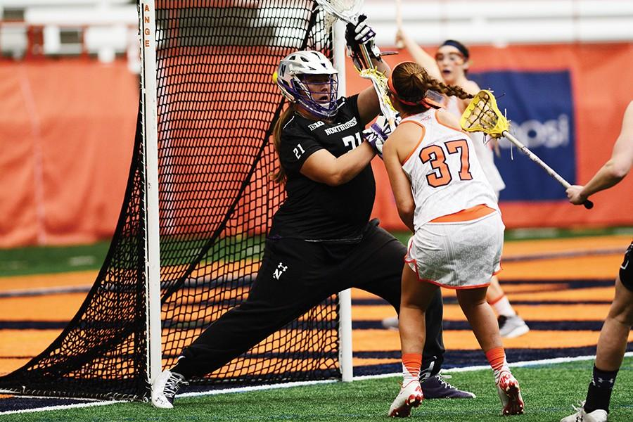 Mallory Weisse attempts to save a shot from an opposing Syracuse player. The freshman goalie made 7 saves in Sunday's loss.
