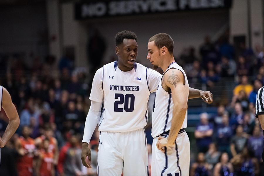 Scottie Lindsey (left) consults with teammate Tre Demps. The former was a sparkplug for the Cats off the bench, scoring 10 points.