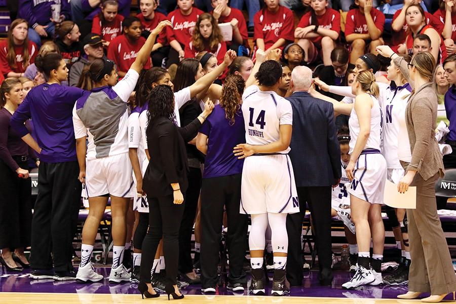Northwestern women's basketball team gathers around the bench during a timeout. The Wildcats have largely disappointed this season after reaching the NCAA Tournament last year.