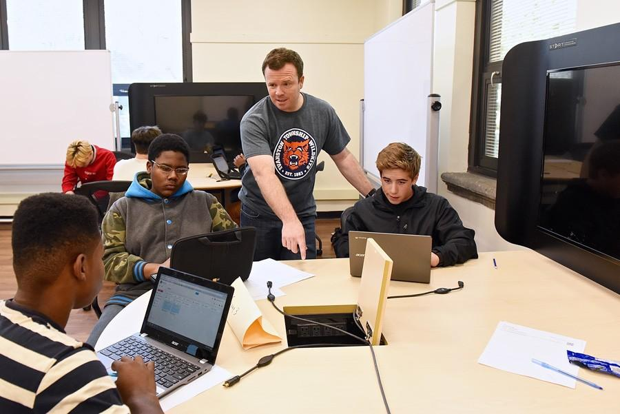 Ross Freeland works with students at Evanston Township High School. He taught several courses in the math department in addition to assistant coaching the varsity baseball team before his death on March 14.