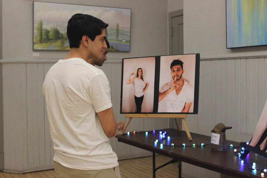 Students observe photography of Unity models displayed at a gallery night at the Noyes Cultural Arts Center. The event was held by Unity Charity Fashion Show and NU Active Minds to support the removal of negative mental health stigmas.