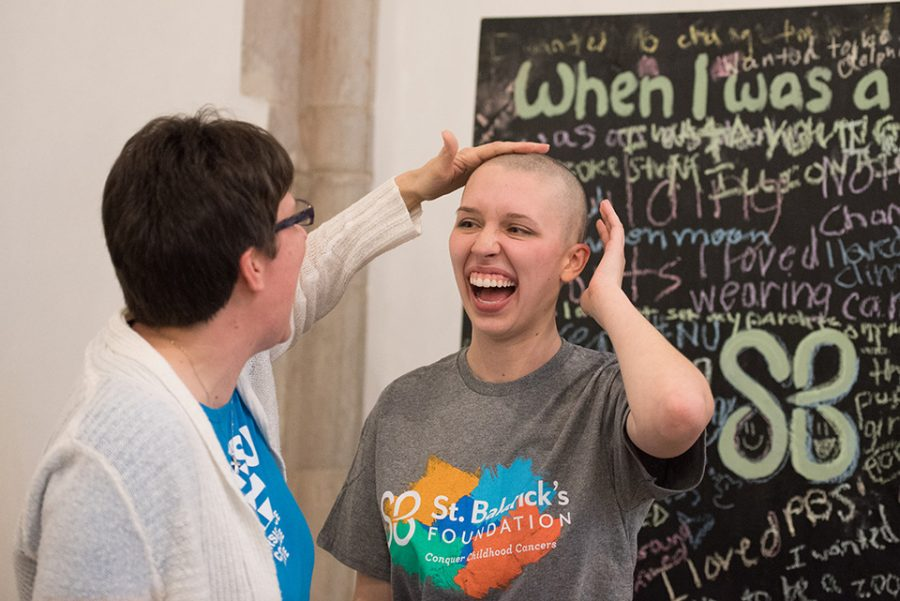 Weinberg sophomore Bethany Ketchem (right) shares a moment with her mother after getting her head shaved Saturday to support St. Baldrick's, a pediatric research foundation.