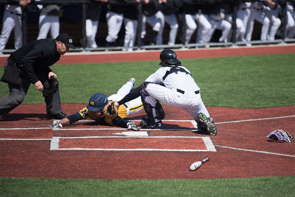 Jack Claeys tags a Michigan runner out at the plate. The sophomore catcher scored 2 of Northwestern's 9 runs in Sunday's loss.