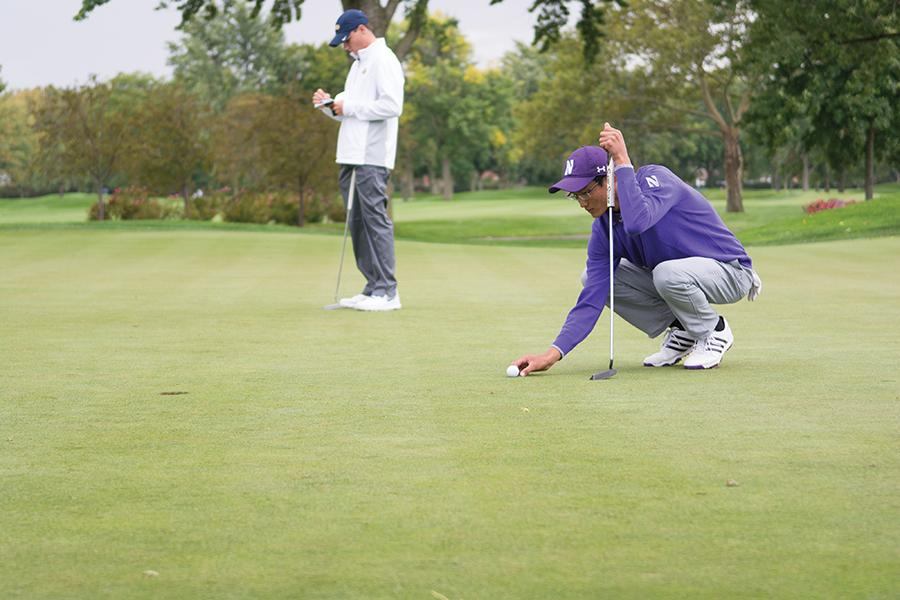 A Northwestern golfer lines up his putt. The Wildcats finished 6th at the Big Ten Championships, led individually by sophomore Dylan Wu at 3-under.