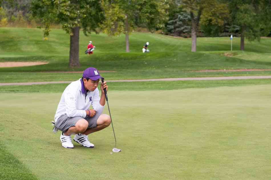 Dylan Wu squats on the green before a putt. The sophomore finished 18th in last year's Big Ten Championships.