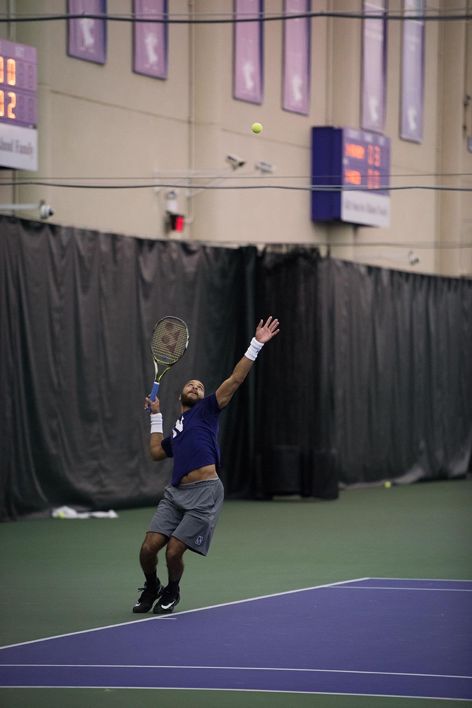 Sam Shropshire tosses the ball before a serve. The junior won his singles match against Penn State on Sunday in straight sets.