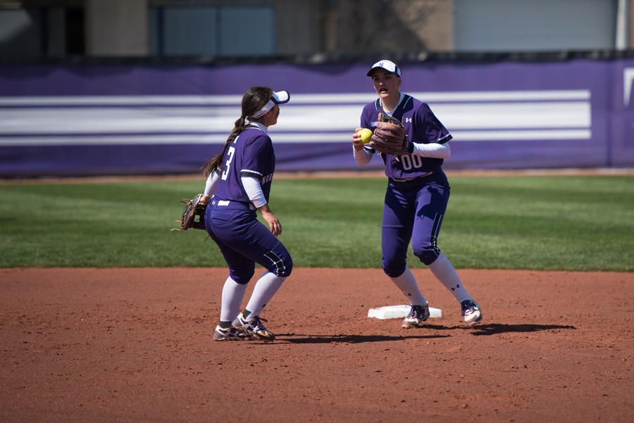 Andrea Filler (right) and Brooke Marquez regroup after fielding the ball. Filler leads the Wildcats in slugging percentage and is tied for first in home runs.