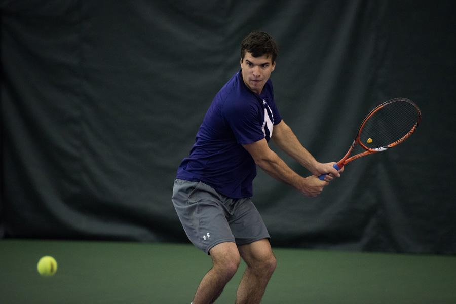 Konrad Zieba readies a backhand return. The junior was defeated in his singles match in the Wildcats' loss to Illinois on Saturday.