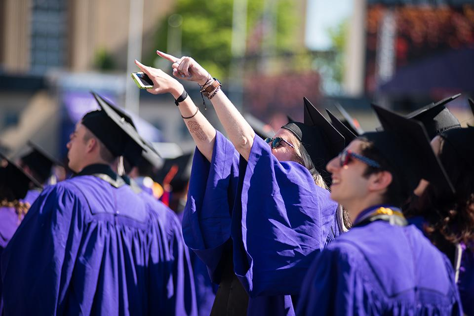 A graduating student walks into Ryan Field and points at the audience. About 15,000 family members, friends and loved ones filled the seats in Ryan Field on Friday morning for this year's commencement ceremony.