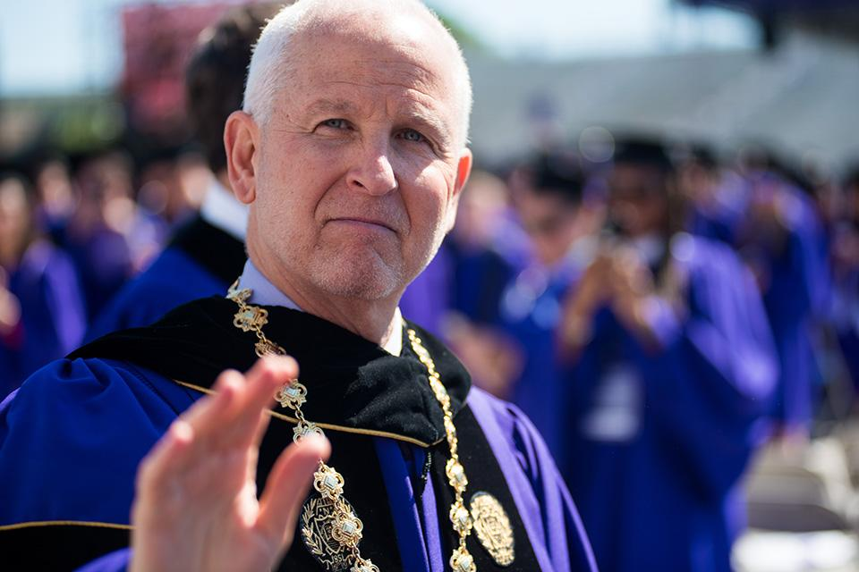 University President Morton Schapiro waves to the audience as he makes his way into Ryan Field. During the ceremony, Schapiro told students to thank their family members and friends for their support through their time at Northwestern.