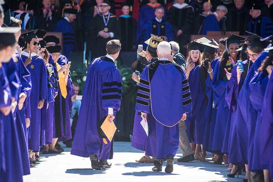 "Schapiro and ""Late Night"" host Seth Meyers take a selfie with a student while marching to the stage. Meyers (Communication '96) was this year's commencement speaker."