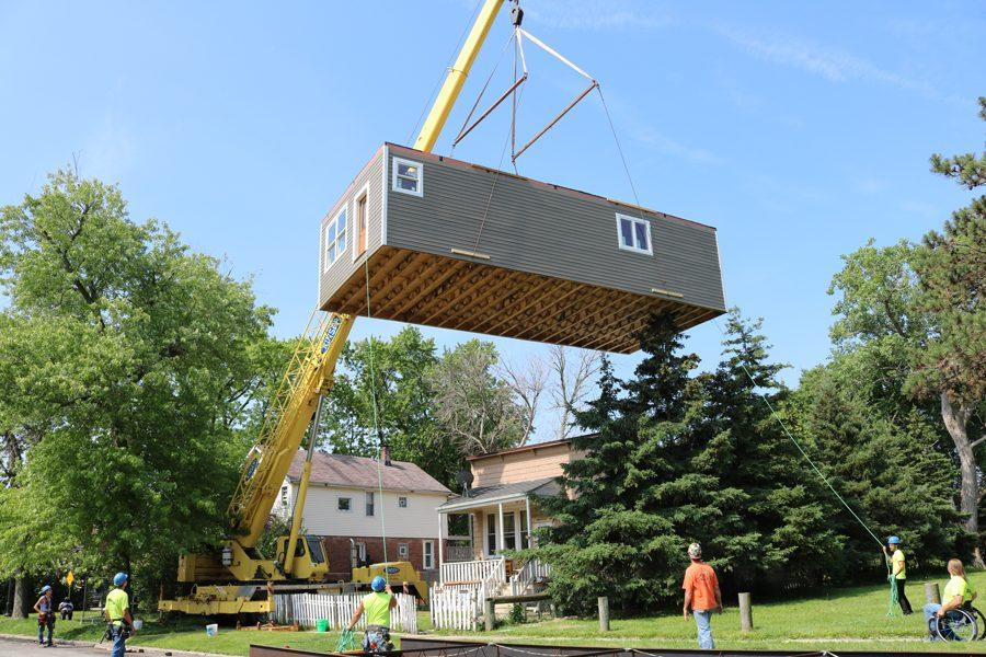 Construction+workers+lift+and+transport+the+first+floor+of+the+home+built+by+students+in+the+Evanston+Township+High+School+course%2C+Geometry+in+Construction.+The+entire+home+was+two-stories+and+approximately+1%2C500+square-feet.