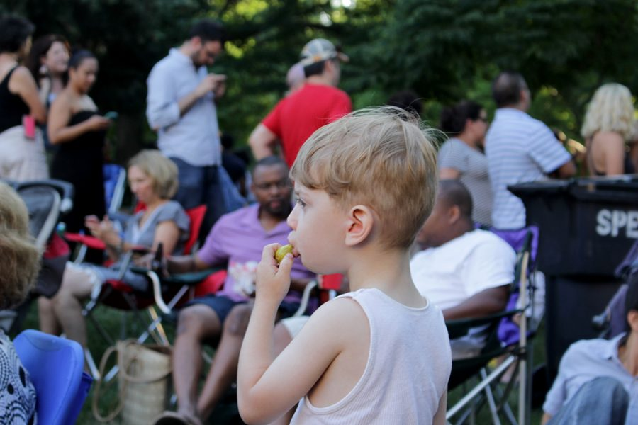 Three-year-old Laszlo Harris chows down on a pickle from one of the trucks while listening to the live music.