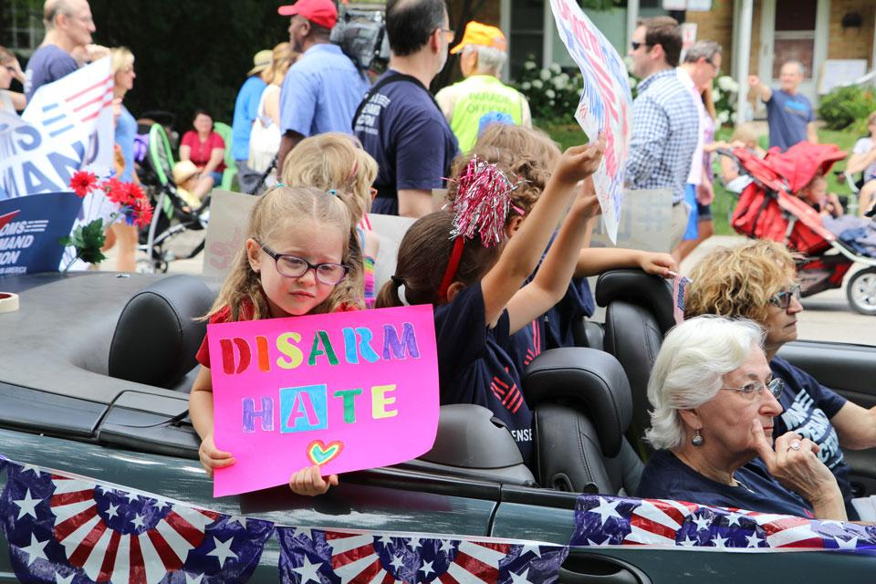 Members of Evanston's Moms Demand Action for Gun Sense in America and young children hold signs as they take part in the city's Fourth of July parade. This is the first year the group brought a float to accompany participants as they marched the parade route.