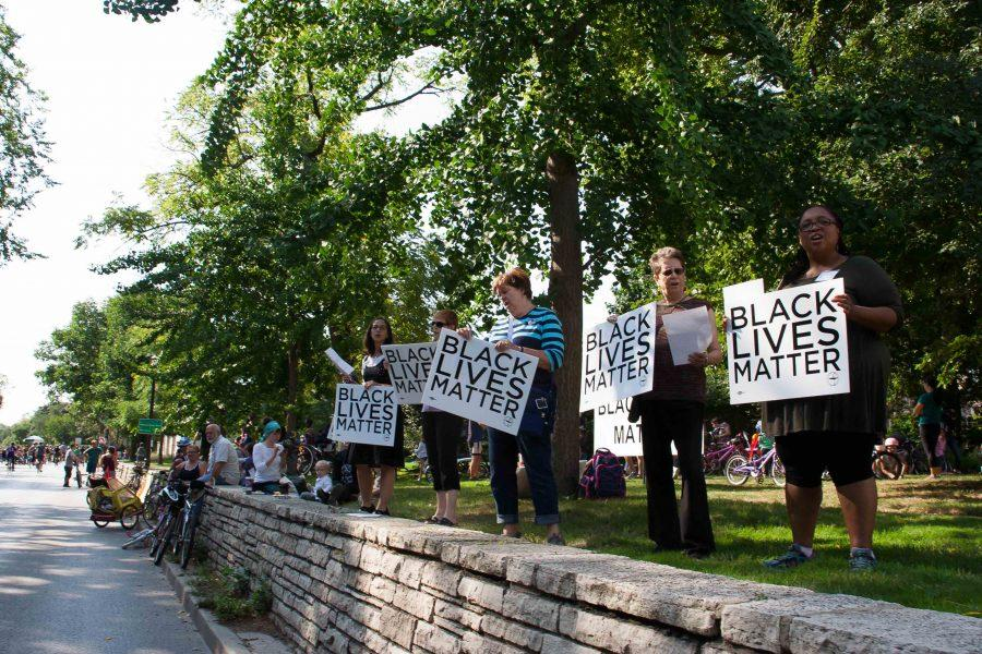 Activists hold Black Lives Matter signs along Ridge Avenue during the Bike the Ridge Event. The ride took place between Howard and Church streets and allowed residents to bike on the road, which is usually closed to cyclists.