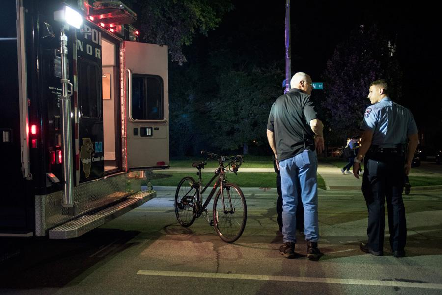 Police stand next to an ambulance and bike involved in an accident on Sheridan Road Thursday. An 18-year-old Northwestern student was killed after an accident with a cement truck while biking.