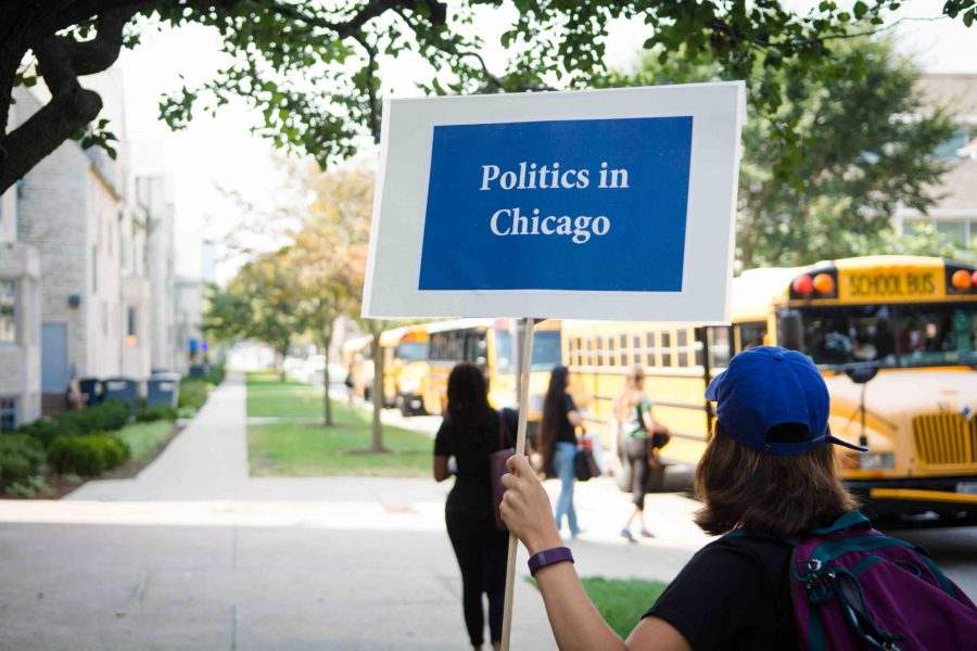 A student holds a sign guiding Northwestern students to buses for NU in Chicago, a neighborhood exploration day. The program, run by the Center for Civic Engagement, aims to connect students with resources and experiential learning in Chicago.