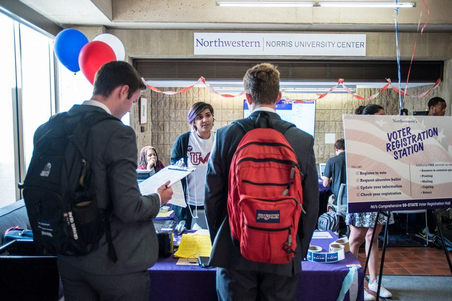 NU Votes volunteers speak to students at a voter registration booth in Norris on Monday. A new online voter registration tool enabled Northwestern to register 96 percent of eligible voters in the freshmen class.