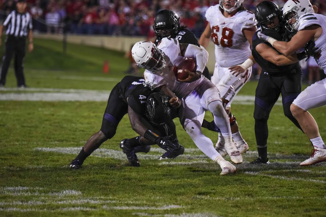 Jared McGee (left) attempts to tackle opposing quarterback Tommy Armstrong Jr. The Nebraska signal caller ran for a career-high 132 yards.