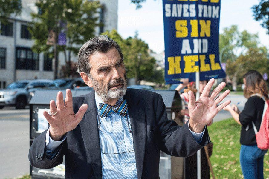 Jed Smock preaches to NU students about sin during a demonstration at The Arch on Monday. Smock is the president and founder of The Campus Ministry USA, a conservative religious group from Terre Haute, Indiana.